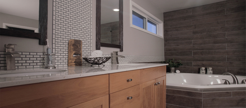 Bathroom Remodeling. Two contrasting types of tiles are used on the wall. The cabinetry complements the walnut finishes of the tile.