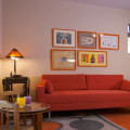 Orange sofa, orange rug, and orange picture frames for pop of color