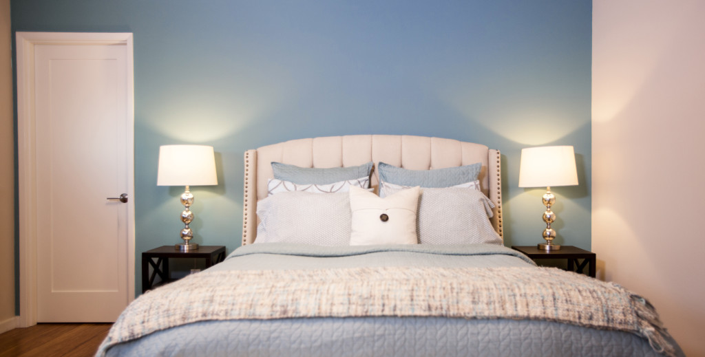 Light blue accent wall brings pop of color to bedroom